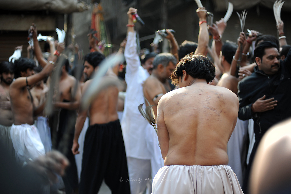 Men are hitting themselves with ceremonial knives during Ashura. Ashura commemorates a day of mourning for the death of Hussein ibn Ali, the grandson of the Prophet Muhammad, at the battle of Karbala.  Shias consider Hussein the third Imam and the rightful successor to Muhammad. The grief for his death is demonstrated by the self-flagellation. Lahore, Pakistan, 2009