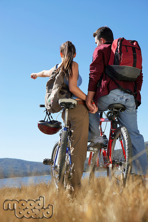Young Couple standing with mountain bikes holding hands back view.
