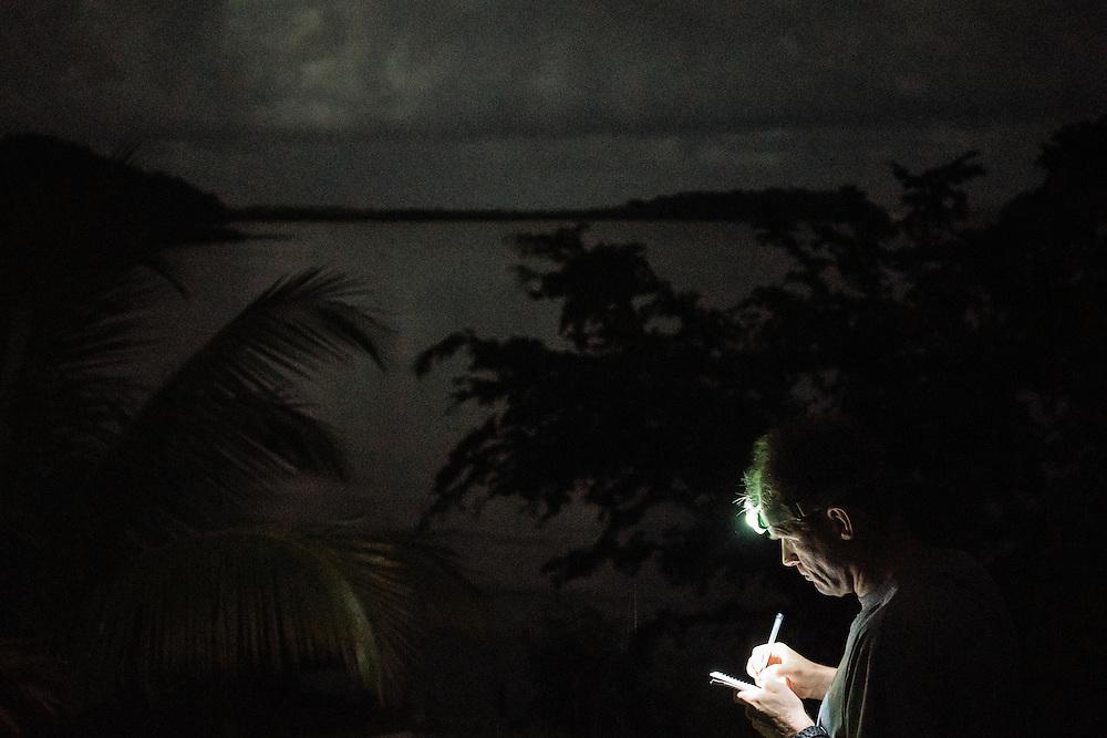 Ornithologist Martjan Lammertink writes notes before sunrise Taco Bay on Jan. 27, 2016.