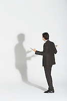 Young businessman standing arguing with own shadow