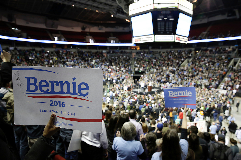 Supporters hold up signs at a rally for Democratic presidential candidate Bernie Sanders at Key Arena on March 20, 2016 in Seattle.  AFP PHOTO/JASON REDMOND