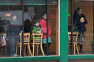 Middletown, New York - People watch through a restaurant window as members of St. Joseph's Church march through the city during the festival of Nuestra Senora de Guadalupe on Sunday, Dec. 9, 2012.