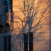 Shadows cast upon an old ornate building in sunset light.