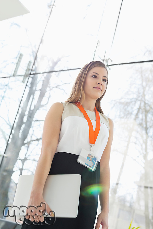 Beautiful businesswoman holding laptop by glass wall in office