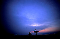 Two people watch the sunset after surfing along the  coast of Michoacan , Mexico.<br />