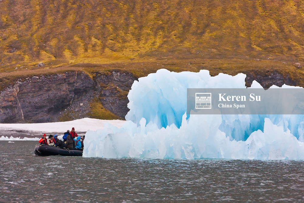 Tourists on zodiac photographing the iceberg, Hornsund, Spitsbergen's southernmost fjord, Norway