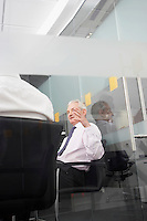 Two businessmen sitting in office behind glass wall back view