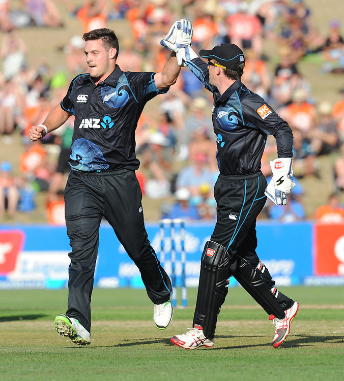 New Zealand's Mitchell McClenaghan, left, high fives with New Zealand's Luke Ronchi after dismissing India's Rohit Sharma for 3 in the first one day International cricket match, McLean Park, New Zealand, Sunday, January 19, 2014. Credit:SNPA / Ross Setford