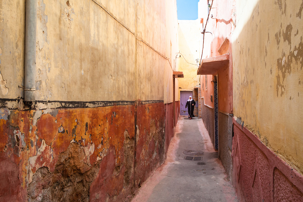 Arab muslim woman, wearing a white headscarf and a traditional black djellaba, in a colorful alley of the old city of Salé, near Rabat, Morocco.
