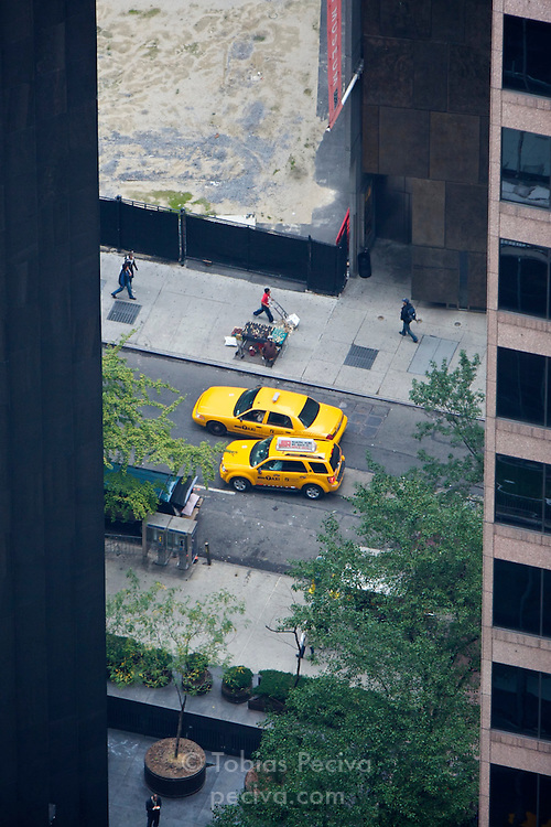 Two taxis jostle for position on a street in midtown Manhattan, New York.
