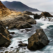 Waves crash against the rocky cliffs of Big Sur along the Central Coast of California.