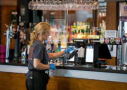 © Licensed to London News Pictures. 04/07/2020. London, UK. A woman cleans the bar at The Ice Wharf pub at Camden Lock, North London as Pubs, bars, cafes and restaurants are allowed to fully open for the first time since lockdown. Photo credit: Ben Cawthra/LNP