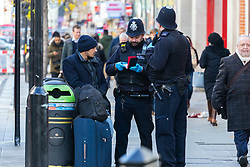 Police officers detain a man on Oxford Street as Eastern European beggars and street performers take advantage of the UK's relative wealth, squeezing opportunities for the UK's own homeless. London, December 13 2018.