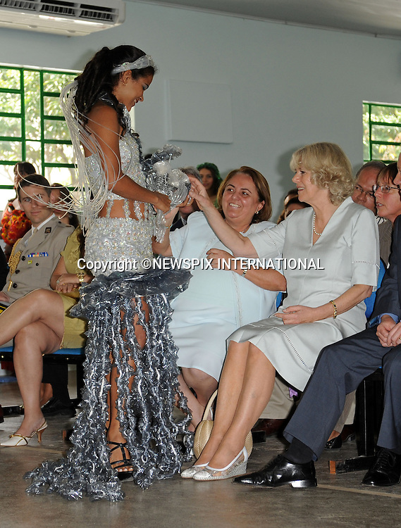 """CAMILLA, DUCHESS OF CORNWALL.Visits the Municipal Centre for Art and Education on a poor area of Manaus where the Duchess had a touching moment with one of the children of """"Curumim na Lata"""" (Children of the can-percussion) holding his hand..The Duchess also watched a fashion show, an experimental youth orchestra and a ballet. The centre seeks to use recycled goods in innovative ways..The clothes modeled by local girls in the fashion have been made from recycled material including bottle lids and crisp packets.The Duchess was wearing an Anna Valentine silk shift dress (Pale blue with white beaded detail)..Forth day Brazil on the second leg of their South American Tour, Manaus, Brazil_14/03/09......Mandatory Credit Photo: ©DIAS-NEWSPIX INTERNATIONAL..Please telephone : +441279324672 for usage fees..**ALL FEES PAYABLE TO: """"NEWSPIX INTERNATIONAL""""**..IMMEDIATE CONFIRMATION OF USAGE REQUIRED:.Newspix International, 31 Chinnery Hill, Bishop's Stortford, ENGLAND CM23 3PS.Tel:+441279 324672  ; Fax: +441279656877.Mobile:  07775681153.e-mail: info@newspixinternational.co.uk"""