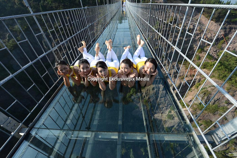 YUEYANG, CHINA - NOVEMBER 05: (CHINA OUT) <br /> <br /> 100 Girls Do Yoga On Glass Suspension Bridge <br /> <br /> Yoga enthusiasts practice on a glass suspension bridge at the Shiniuzhai National Geological Park on November 5, 2015 in Pingjiang County, Yueyang City, Hunan Province of China. 100 yoga enthusiasts practice on the glass suspension bridge with a length of 300 meters and a maximum height of 180 meters at the Shiniuzhai National Geological Park in Pingjiang. <br /> ©Exclusivepix Media