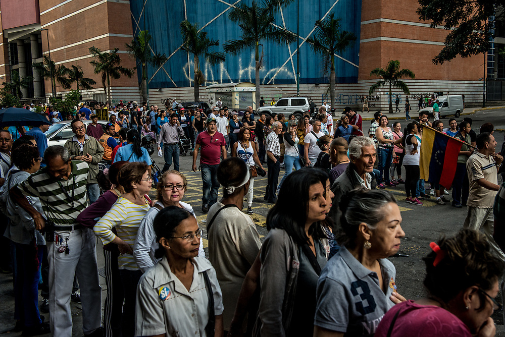 CARACAS, VENEZUELA - JULY 16, 2017: Hundreds of people wait in line to vote in Caracas. Today, at over 2,000 polling locations, Venezuelans participated in a symbolic vote, called by the political opposition to the Socialist government. Ballots had three questions: ONE - Do you refuse the government's plans for a new constituent assembly, without prior approval from the people, TWO - Do you demand that government employees obey and defend the 1999 Constitution and respect the decisions of the National Assembly, and THREE - Do you approve that powers should be established by the Constitution, and that we should have free and transparent elections? The opposition held this vote, as a massive act of civil disobedience to show that the people disapprove of the government. For over 3 months, anti-government protests have raged across Venezuela.  PHOTO: Meridith Kohut