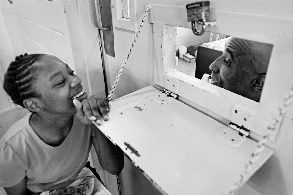 Charnese Zanders, 12, visits her father, Van Morris, through a small window in the locked door of his hospital room. Zanders was reunited with her father through the Angola Prison hospice program. Morris, who is diagnosed with colon cancer, remains in lockdown because of a history of disruptive actions. Regardless, Angola Warden Burl Cain encourages his staff to facilitate family visitation. ?Family visitation is not about pampering inmates,? says Melody Eschete, the Angola's hospice coordinator. ?It is preventative psychiatry.  We hope to help them repair wounds with their loved ones. This helps the grieving process for their family, who are the unidentified victims of crime.?