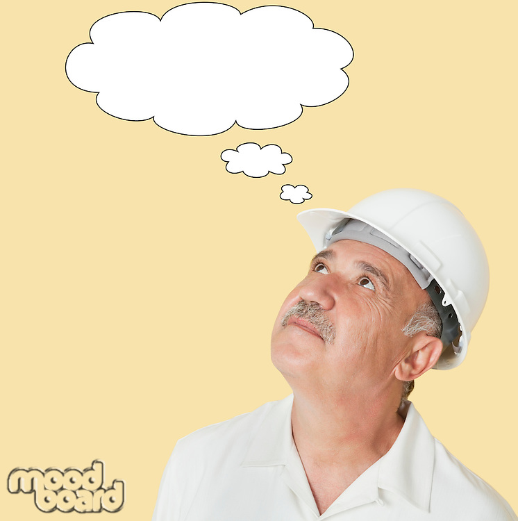 Senior construction worker with hardhat looking up at speech bubble over yellow background