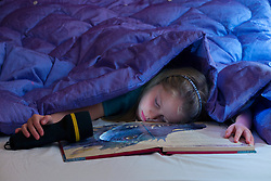 Girl sleeping in bed under blanket. Dark room, battery lamp and book.