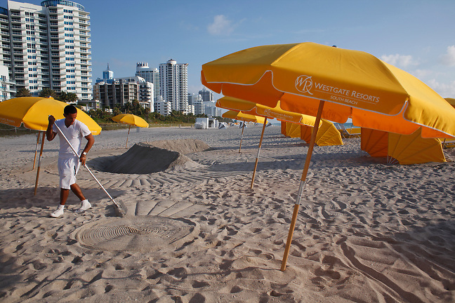 4/3/13---Miami Beach, Florida---Photo by Angel Valentin<br /> Julio Pagan, a beach attendant for Westgate Resorts, works on a sand design after setting up beach umbrellas, cabanas and chairs on the sands of Miami Beach near 36 street in the early hours of the morning.