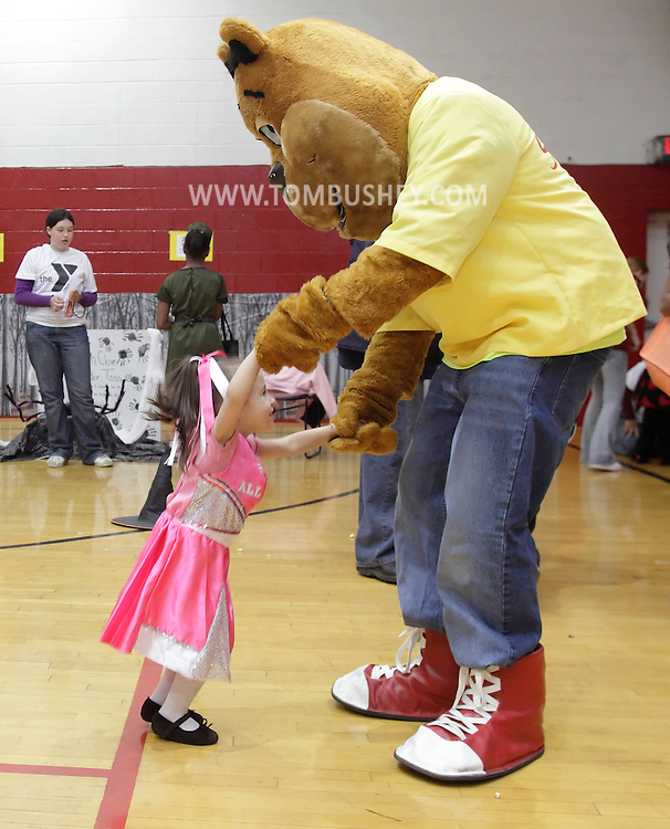Middletown, New York - A little girl wearing a costume dances with Scrunchy, the ShopRite mascot, during the Family Fall Festival at the Middletown YMCA on Oct. 23, 2010.