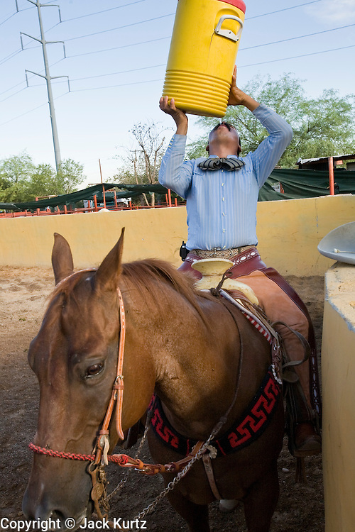 31 AUGUST 2007 -- PHOENIX, AZ: HECTOR LUNA, a competitor at the Congreso y Campeonato Nacional Charro in Phoenix, AZ, Friday, August 31, drinks from a water barrel during a break. The high in Phoenix Friday was about 110 degrees. The event is the US championship for the Mexican Federacion Mexicana de Charreria. The winners of the US championship go on to compete in the Mexican Charreada championships in Morelia, Michoacan, Mexico in October. Charreadas are Mexican style rodeos that are popular in Mexican communities throughout the US. As the Mexican immigrant community has expanded throughout the US, the sport has expanded with it. Charreadas are now held as far north as Minnesota and along the US - Mexico border.   Photo by Jack Kurtz