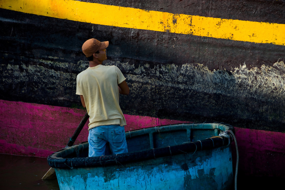 A fisherman docks his boat to collect fish from the fishing vessel.