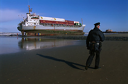 """BLANKENBERGE, BELGIUM - NOVEMBER 9, 2001 - A police officer patrols the beach at Blankenberge, where a cargo ship ran aground. The German cargo ship """"Heinrich Behrmann"""", was beached by heavy seas after losing power to the main engine late Thursday night at Blankenberge. The ship was heading for the port at Zeebrugge from Ireland, and was carrying dry cargo, none of which was hazardous. The salvage company Unie Van Redding - En Sleepdienst N.V. was hired to free the ship. Three unsuccessful attempts were made Friday, the second attempt resulted in the injury of two workers when tug boat cables snapped. The beached ship has attracted the attention of curious tourists. (Photo © Jock Fistick)"""
