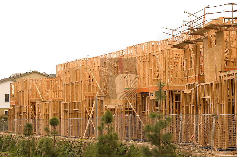 Wood framing of a new housing development with a white sky for copy