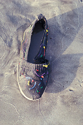 Beach combers abandonded shoe on sand.