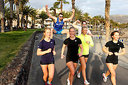 Young sporty people jogging on the beach promenade.