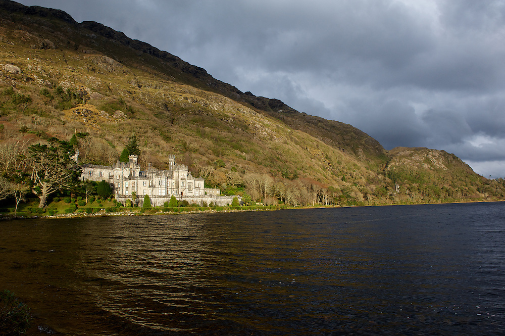 Kyelmore Abbey viewed over the waters of Lake Pollacappul in County Galway, Ireland.
