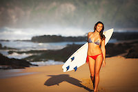 Beautiful young female surfer in bikini, modeling with surfboard in Hawaii.