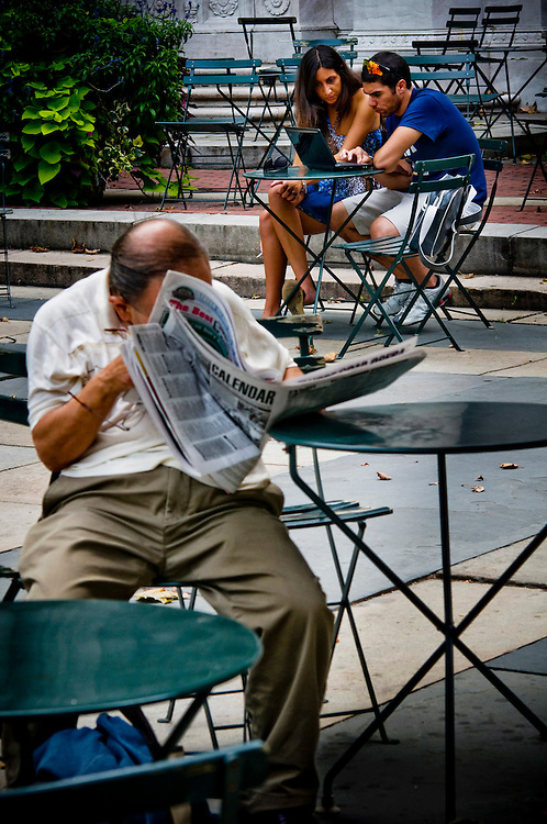 Crisis in the newspaper industry.  New Yorkers and their news reading habits...A young couple reading something online on their laptop in Bryant Park where there is free public wifi internet, while a man is reading the newspaper...Photographer Chris Maluszynski /MOMENT