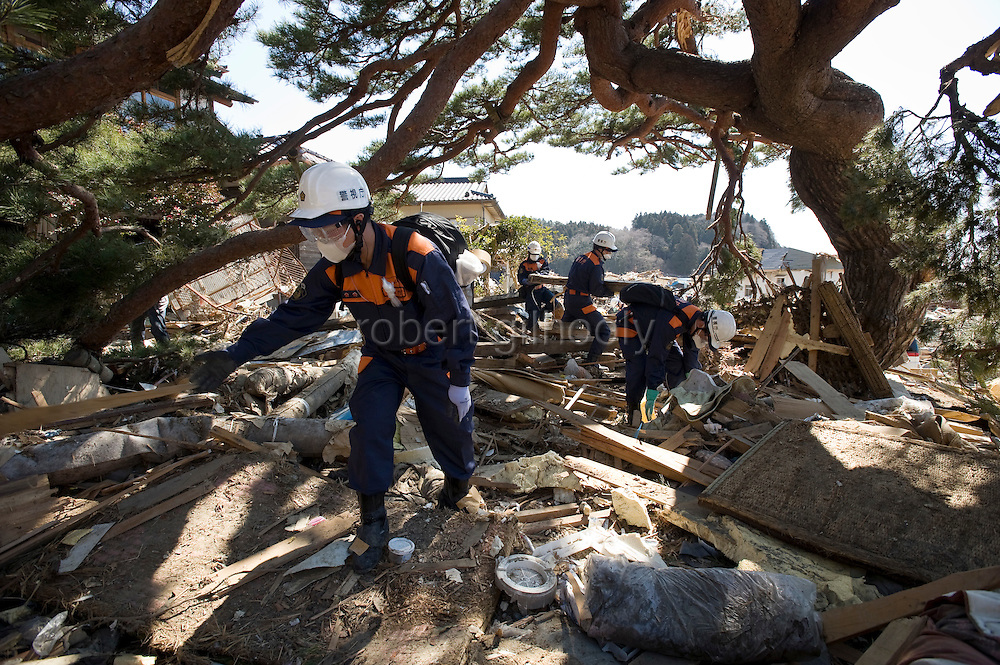 Members of the national police search through the rubble for people still missing following the March 11 magnitude 9 quake and subsequent tsunami in Rikuzentakata on April 6, 2011..Photographer: Robert Gilhooly