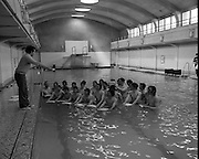 BIM Swimming Lessons For Fishermen..1972..27.05.1972..05.27.1972..27th May 1972..After a recent spate of of accidents at sea where several fishermen had drowned B.I.M.instituted a programme of swimming lessons.Skippers and crews from around the country were encouraged to take part in the hope that safety at sea would improve..Picture shows trawler crews from Skerries beginning their swimming lessons. they are under the watchful eye of instructor Seamus Waters.