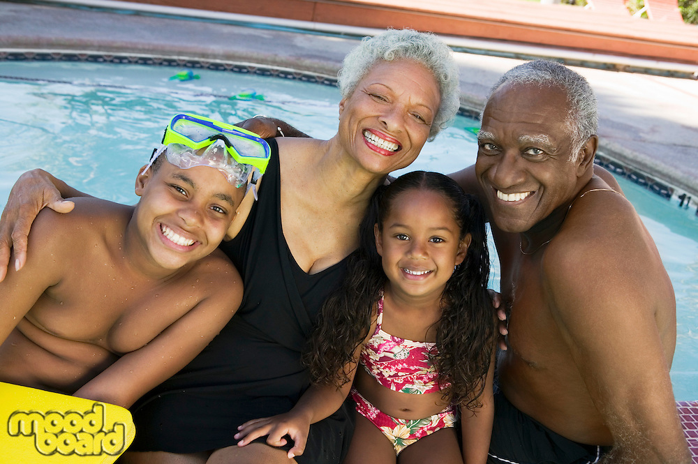 Girl (5-6) boy (10-12) with grandparents at swimming pool portrait.
