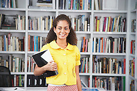 Young woman holding paper material in front of bookshelf smiling