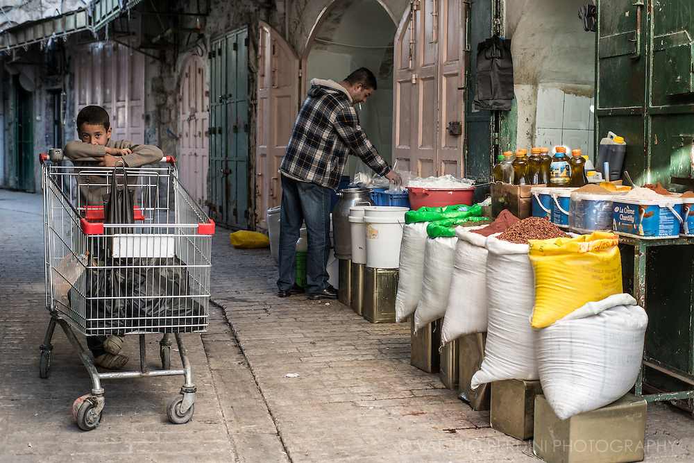 A boy with a trolley in front of one of the few shops still open within the Hebron Old Market.