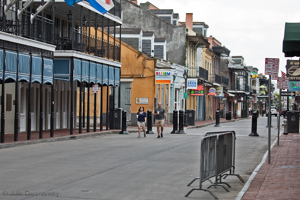 A couple carrying drinks walking down Bourbon Street. in  Orleans French Quarter on March 27, 2020  during a mandatory stay at home order due to the COVID-19 Pandemic. New Orleans , major city, USA