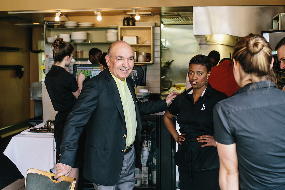 Qayum Karzai, the older brother of Afghanistan's longtime president Hamid Karzai, talks with his staff at b - A Bolton Hill Bistro, one of three restaurants he and his family own in Baltimore, Md. Karzai splits his time between the United States and Afghanistan, running the restaurants in Baltimore while helping govern his home country. CREDIT: Greg Kahn/GRAIN for The Wall Street Journal   SLUG: KARZAI