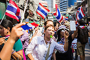 05 JANUARY 2014 - BANGKOK, THAILAND: An anti-government marchers in Bangkok cheer as marchers approach them. Suthep Thaugsuband, leader of the anti-government protests in Bangkok, led the protestors on a march through the Chinatown district of Bangkok. Tens of thousands of people waving Thai flags and blowing whistles gridlocked what was already one of the most congested parts of the city. The march was intended to be a warm up to their plan by protestors to completely shut down Bangkok starting Jan. 13.     PHOTO BY JACK KURTZ