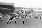 Galway player kicks the ball as Dublin dives in an attempt to block him during the All Ireland Senior Gaelic Football Championship Final Dublin V Galway at Croke Park on the 22nd September 1974. Dublin 0-14 Galway 1-06.