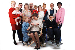 Multiracial group of people including boy with learning difficulties; boy with disability who is wheelchair user and adult with hearing impairment using sign language to communicate with young son,