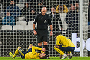 Mike Dean (Referee) looking at Calum Chambers (Arsenal) injured in front of him during the Premier League match between West Ham United and Arsenal at the London Stadium, London, England on 9 December 2019.