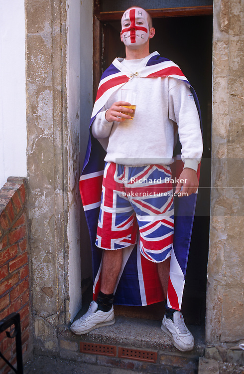 Gathering outside his house in the East End of London, a young football fan whose painted face is in the colours his favourite Tottenham Hotspur Football Club, also wears a Union Jack cape and shorts. He stands in the front doorway of his terraced home to celebrate the 50th anniversary of VE (Victory in Europe) Day on 6th May 1995. In the week near the anniversary date of May 8, 1945, when the World War II Allies formally accepted the unconditional surrender of the armed forces of Germany and peace was announced to tumultuous crowds across European cities, the British still go out of their way to honour those sacrificed and the realisation that peace was once again achieved. Street parties now - as they did in 1945 - played a large part in the country's patriotic well-being.