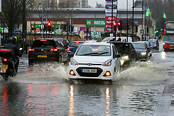 © Licensed to London News Pictures. 20/12/12/019. London, UK. Cars travel through a flood on Green Lanes, Harringay in North London, caused by overnight heavy rainfall and a pipe burst.  Photo credit: Dinendra Haria/LNP