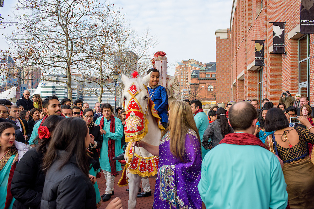 Baltimore, Maryland - December 20, 2014: Eshwan Ramudu rides Chico, a male 22 year-old, Andalusian horse, from Mt. Airy, MD outside the Baltimore Marriott Waterfront Hotel for his baraat. Riding with Eshwan is his bride's nephew Arjun Khanna. By tradition, a young boy, the &quot;sarbala&quot; from the family who rides the with the groom as protection from others who might wish ill upon him. <br /> Trisha Satya Pasricha and Eshwan Ramudu married at the Baltimore Marriott Waterfront Hotel December 20, 2014. <br /> <br /> <br /> CREDIT: Matt Roth for The New York Times<br /> Assignment ID: 30168620A