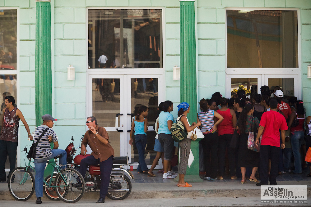 A group of people wait to enter a shop in Baracoa, Cuba on Monday July 14, 2008.