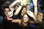 Group of teenage Ravers dancing, arms raised in the air, UK 1990's,